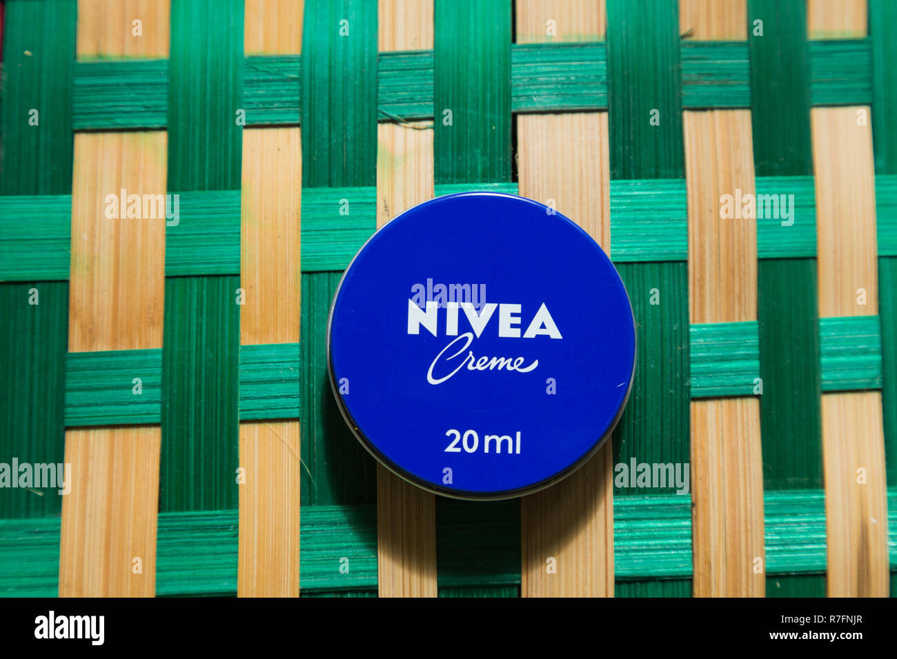 Nivea creme tin place in a green pattern background - Stock Image