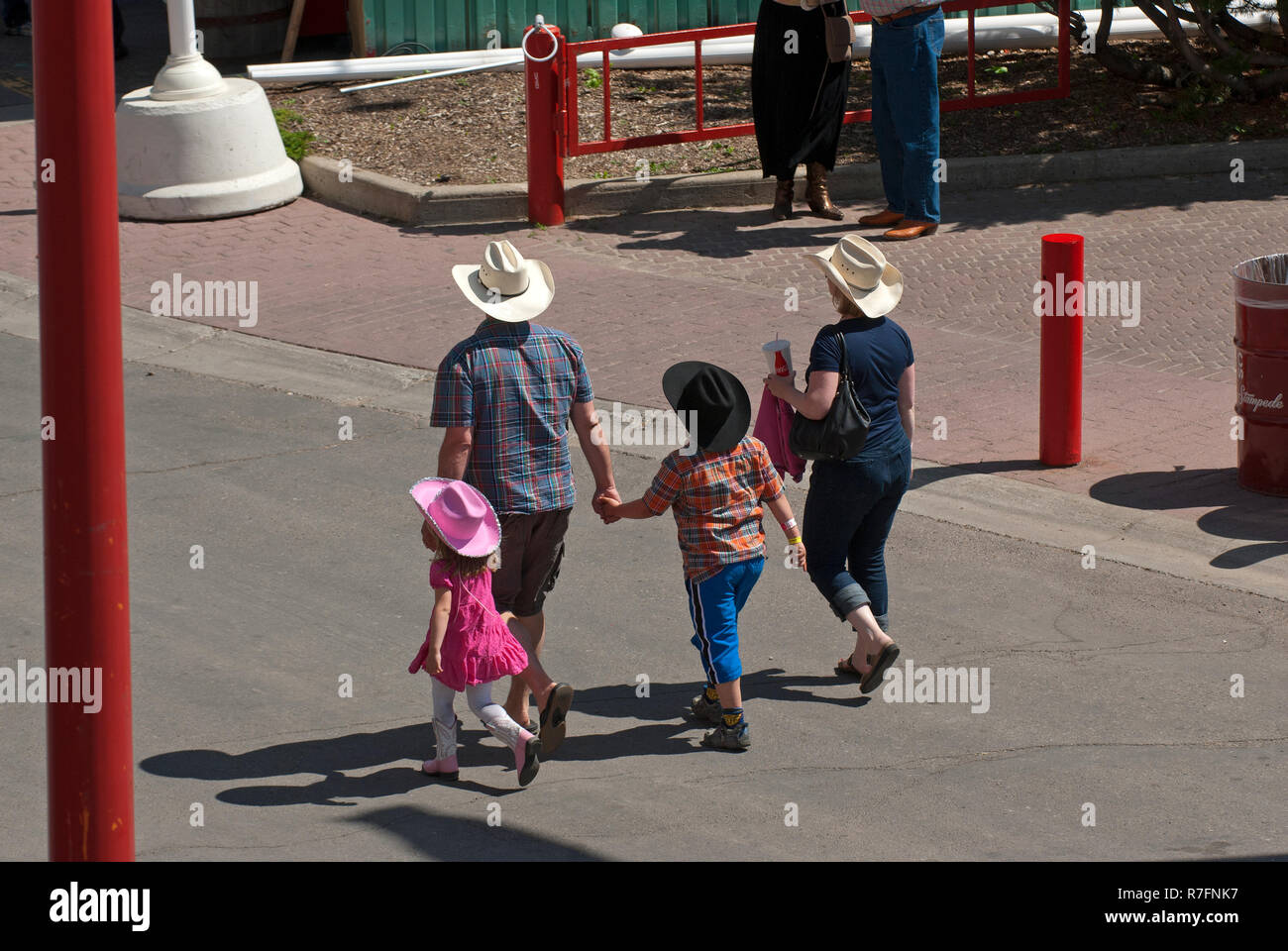 A family walking in Stampede Park during Calgary Stampede show, Calgary, Alberta, Canada - Stock Image
