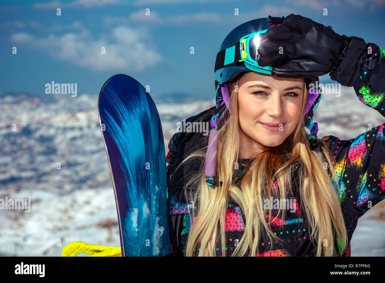 Portrait of a cute blond snowboard trainer in the snowy mountains, extreme winter sport, competition between snowboarders, active wintertime holidays - Stock Image