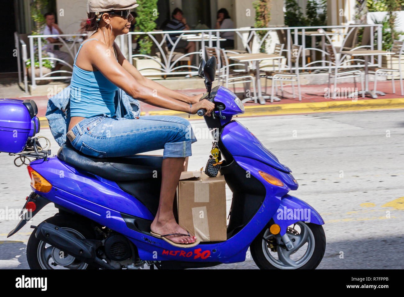 Miami Beach Florida Ocean Drive scooter motorcycle two-wheeled motor vehicle personal transportation low cost urban Black wom - Stock Image