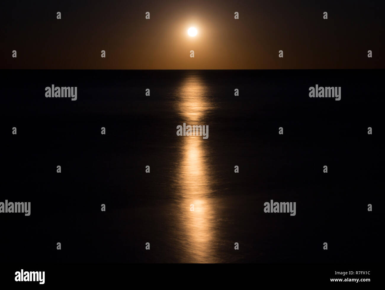 A rising full moon reflecting in the sea - Stock Image