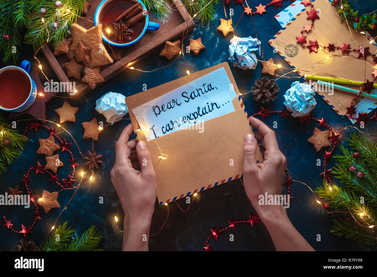 Hands holding a letter to Sant. Beautiful Christmas flat lay with fairy lights, star-shaped cookies, and tea. Dark still life from above with contrast colors and copy space - Stock Image
