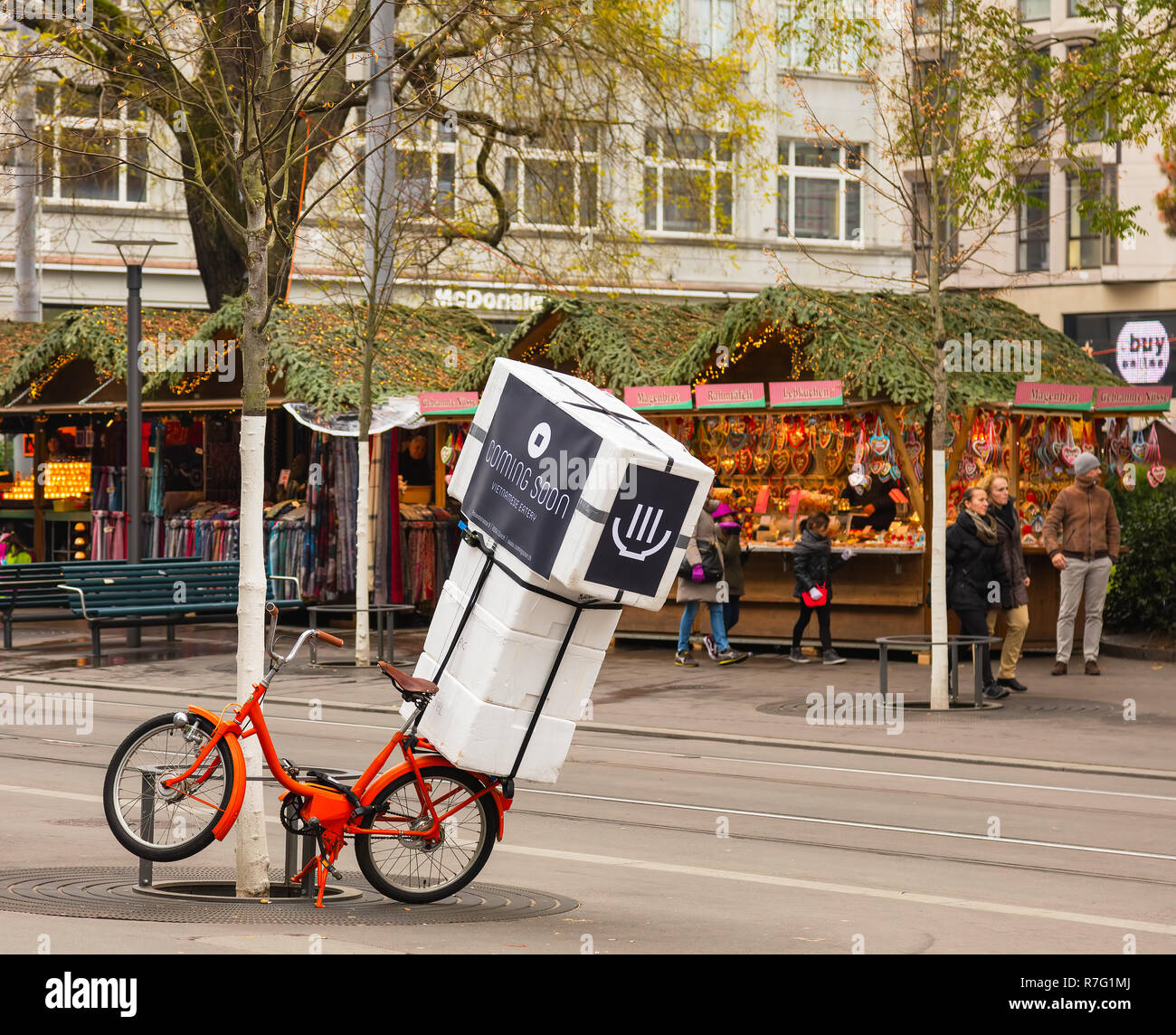Zurich, Switzerland - December 6, 2015: a bicycle used for advertisement on Bahnhofstrasse street in the city of Zurich, people and Christmas market k - Stock Image