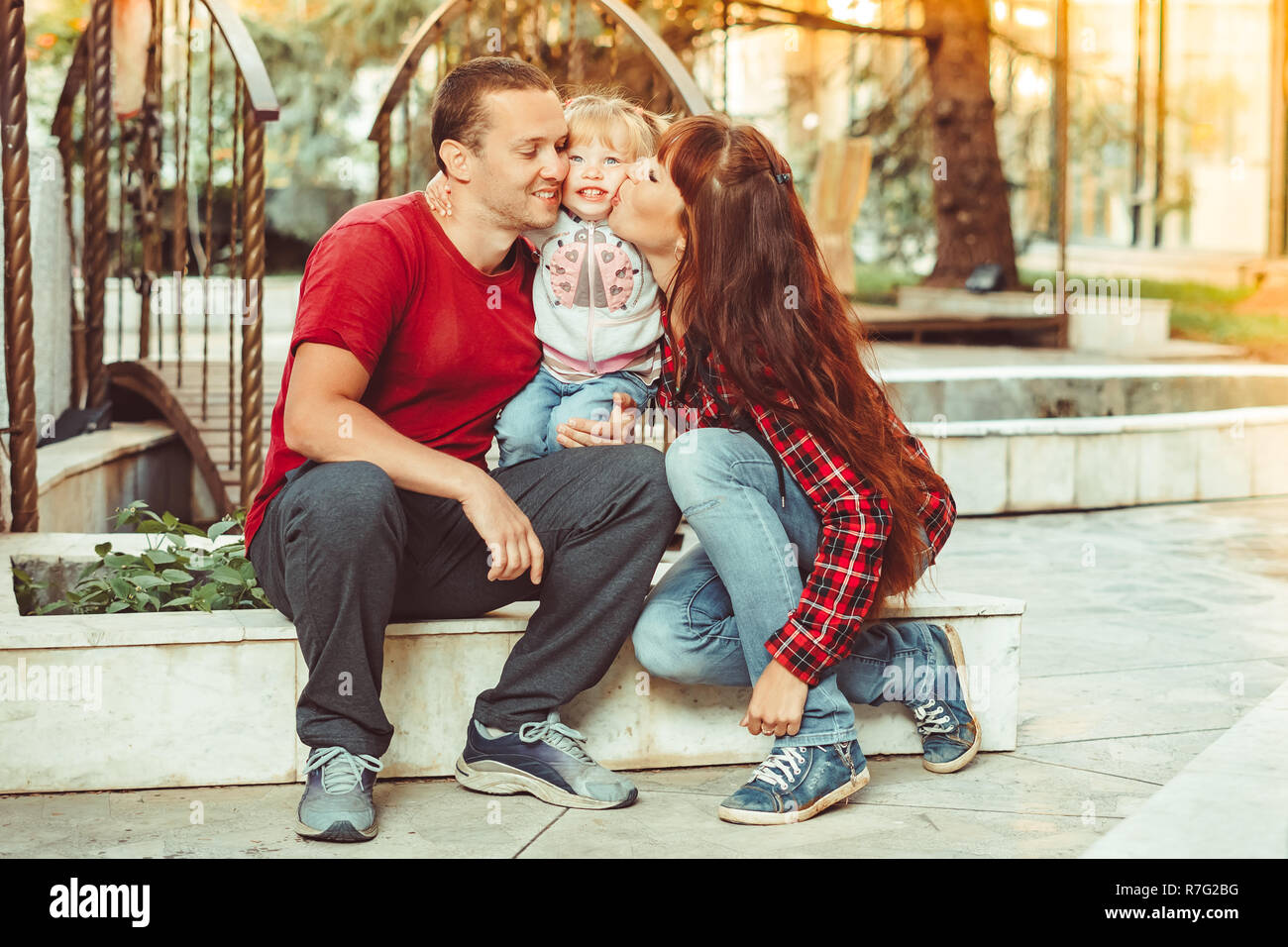 cute little girl and her beautiful young parents looking at the camera and smiling - Stock Image