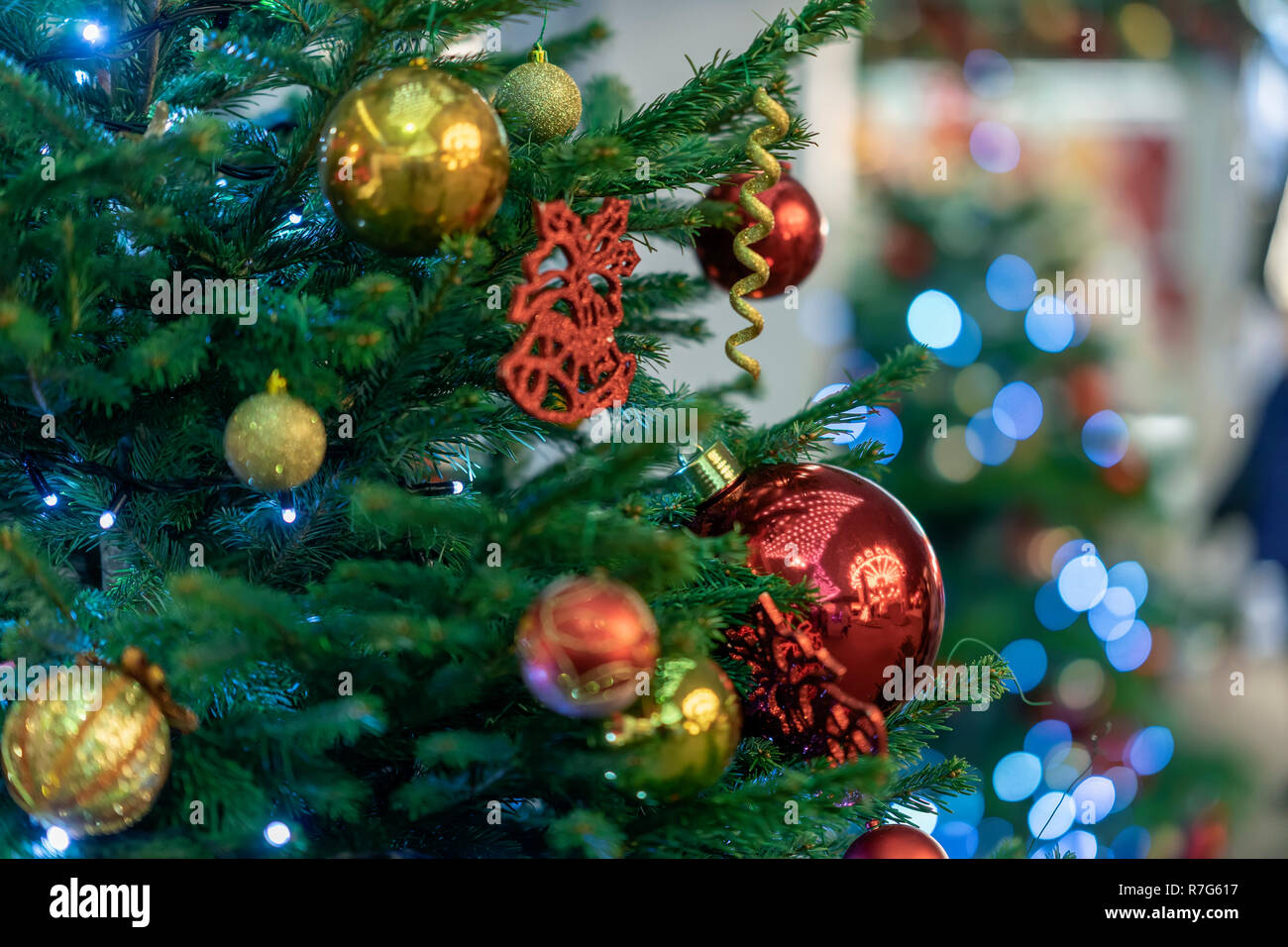Festive christmas tree with bright colorful balls, garlands, decorations close-up. Selective focus. Winter holiday, Happy New Year - Stock Image