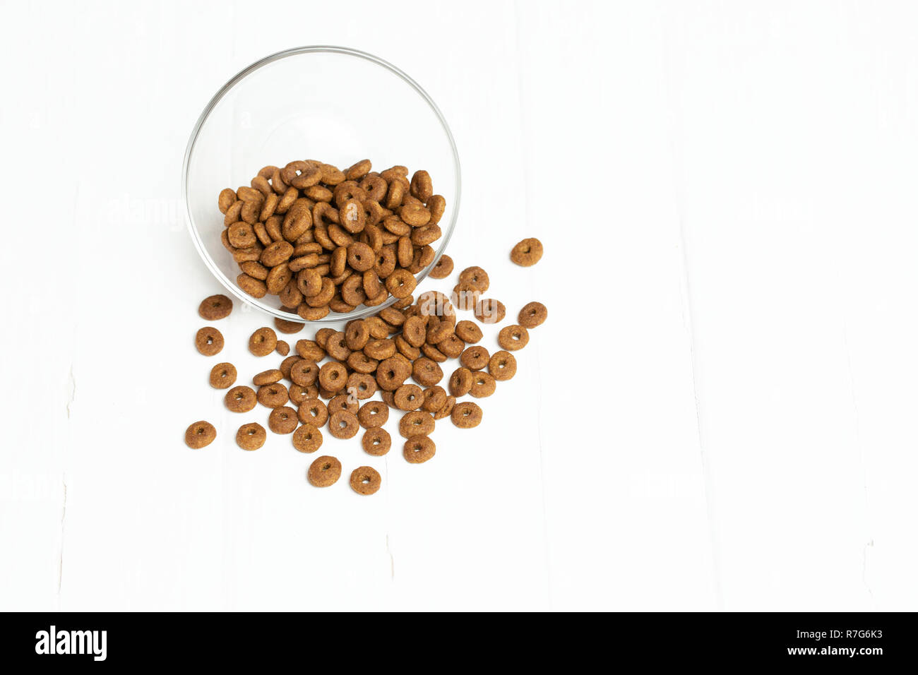 Dry cat food poured out of a transparent bowl on a white background Stock Photo
