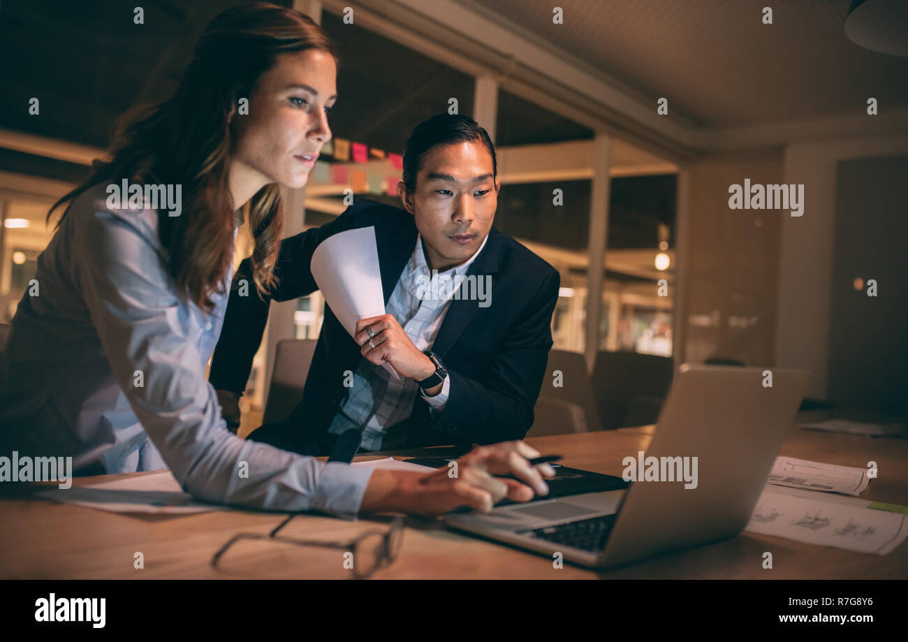 Woman entrepreneur working on laptop sitting with her colleague in office. Business partners working late night to meet project deadlines. - Stock Image