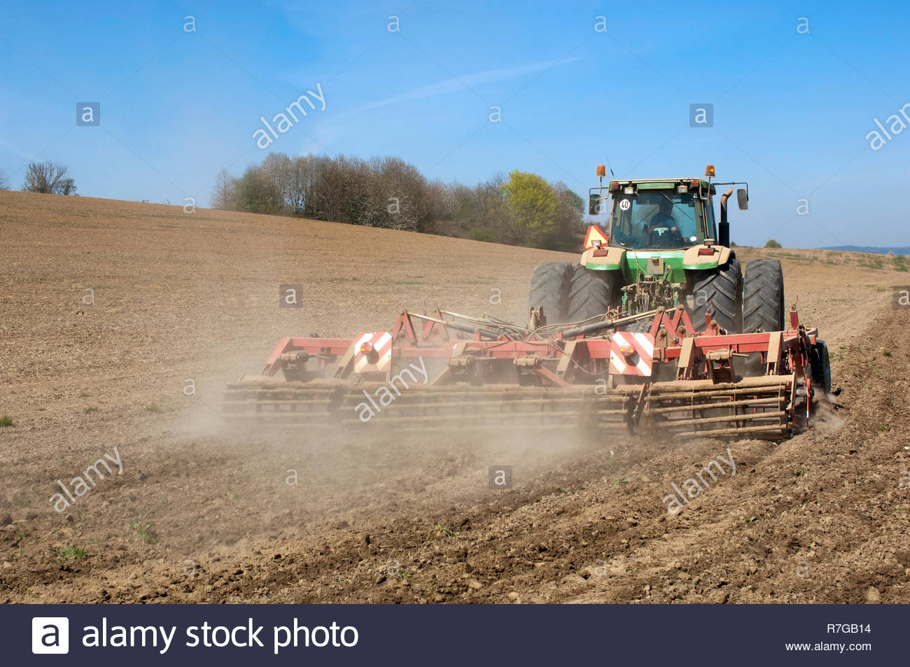Tractor with cultivator prepares field for seeding. Stock Photo