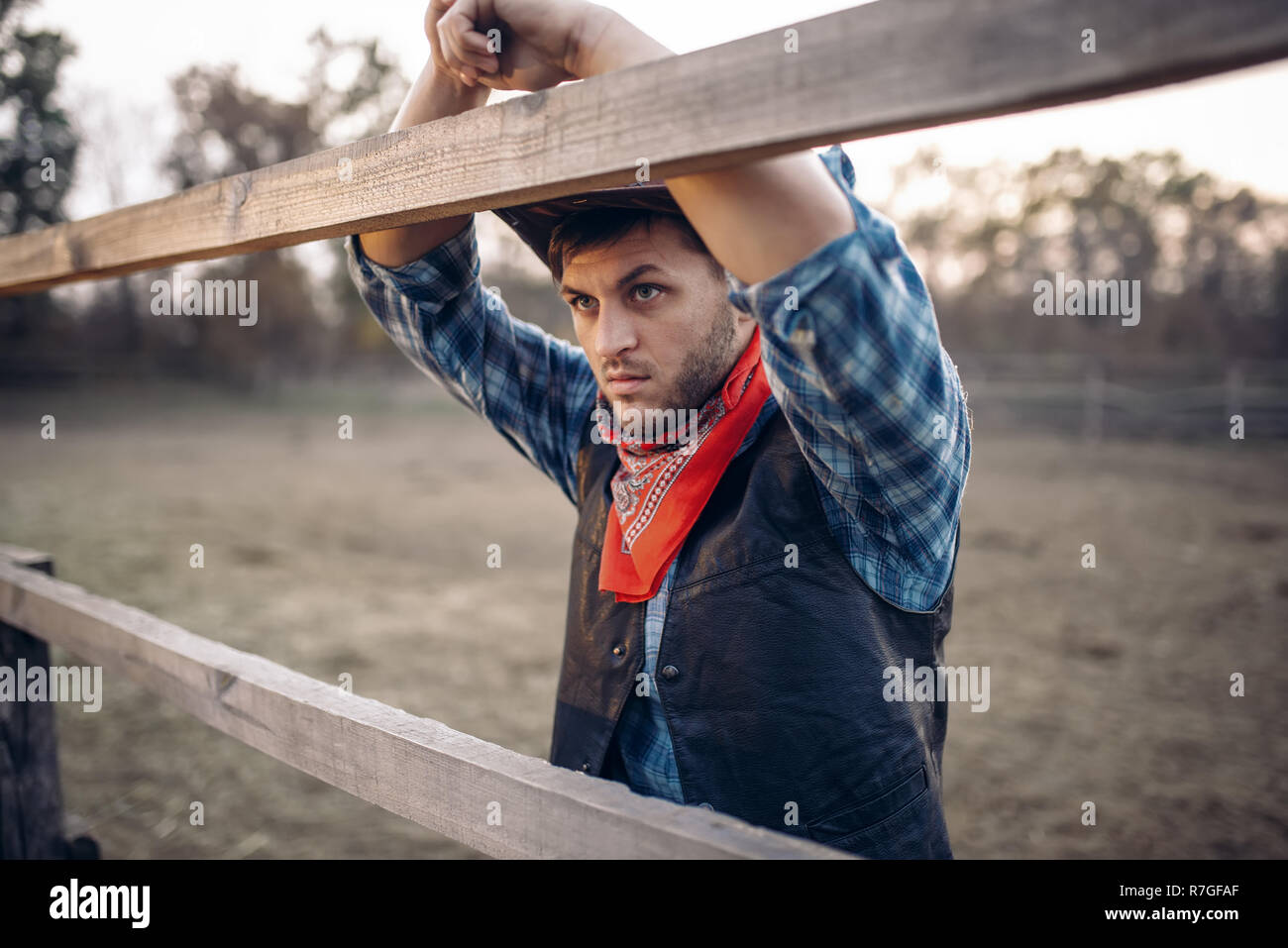 Young cowboy in leather jacket and hat poses on ranch 5add2838b6c2