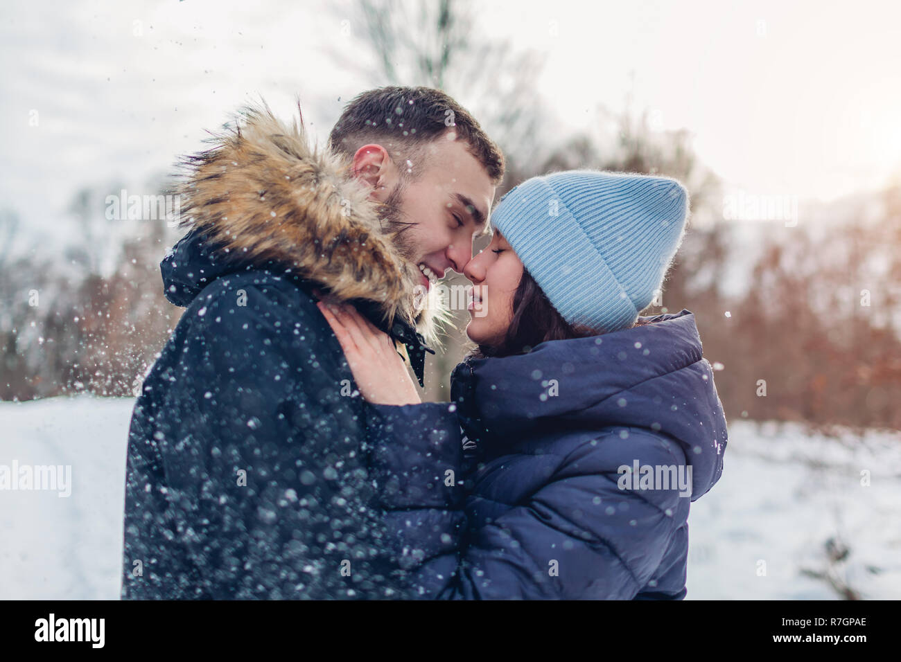 Beautiful loving couple walking and hugging in winter forest. People having fun outdoors under falling snow Stock Photo