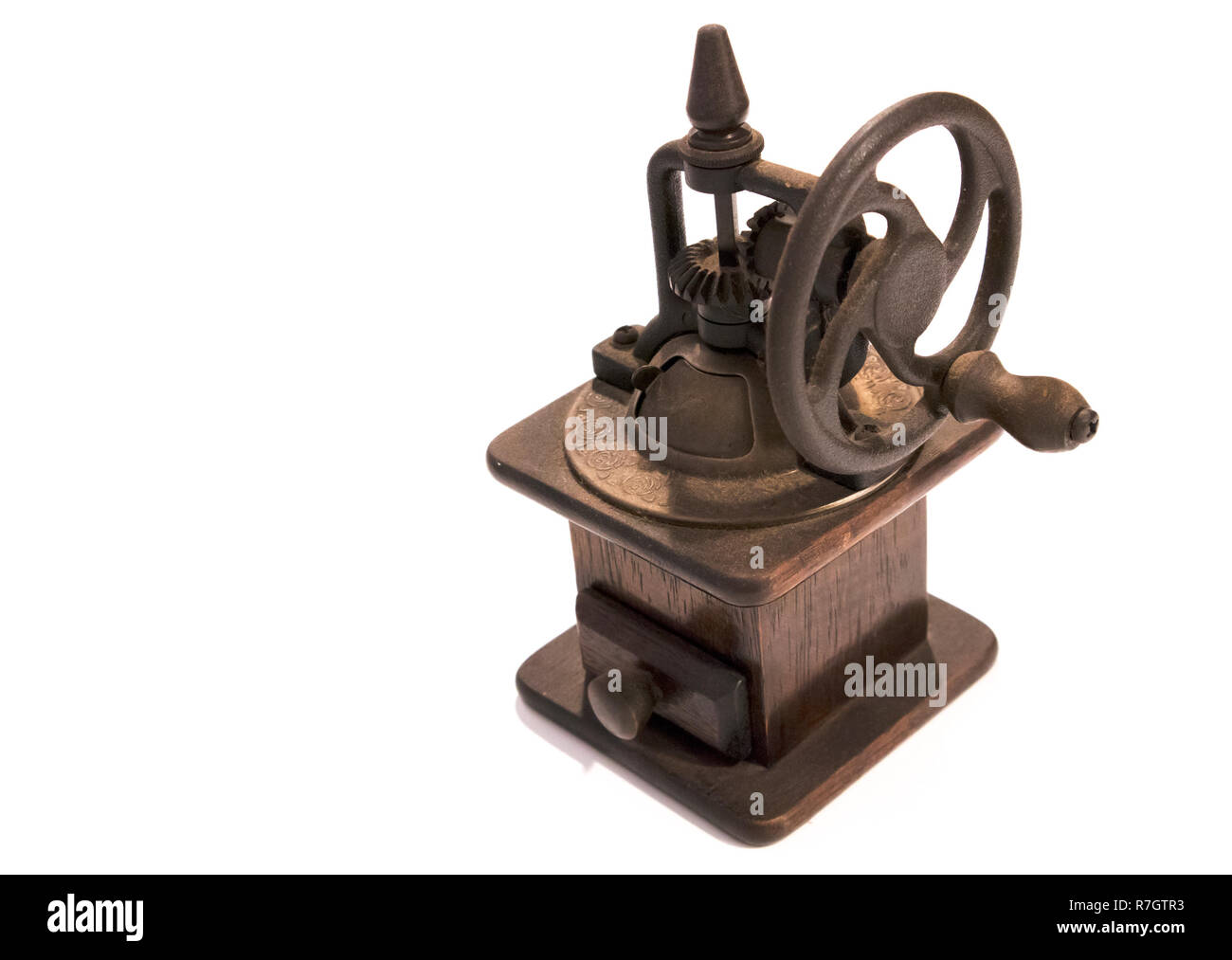 Old manual wooden coffee grinder with gear wheel isolated on white background - Stock Image