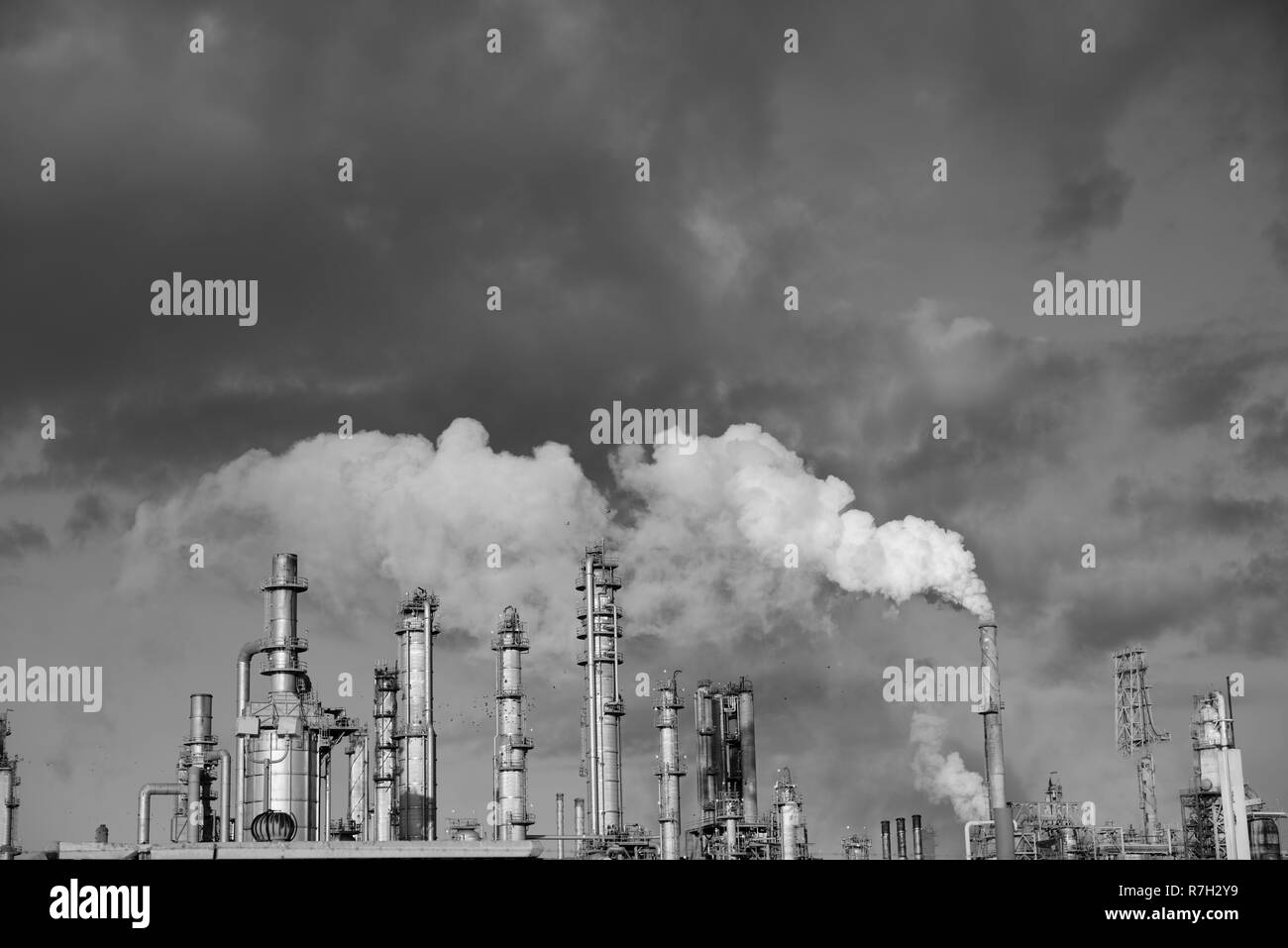 Smoke rising from a complex arrangement of metal towers and pipes at an industrial oil and gas refinery in Corpus Christi, Texas / USA. - Stock Image