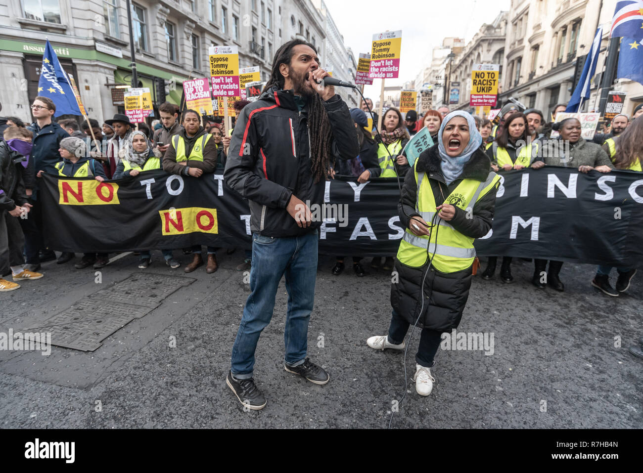 London, UK. 9th Dec, 2018. A united counter demonstration by anti-fascists has to wait for a few minutes on Haymarket until police clear the route. The protest was in opposition to Tommy Robinson's fascist pro-Brexit march. The march which included both remain and leave supporting anti-fascists gathered at the BBC to to to a rally at Downing St. Police had issued conditions on both events designed to keep the two groups well apart. Credit: Peter Marshall/Alamy Live News Stock Photo