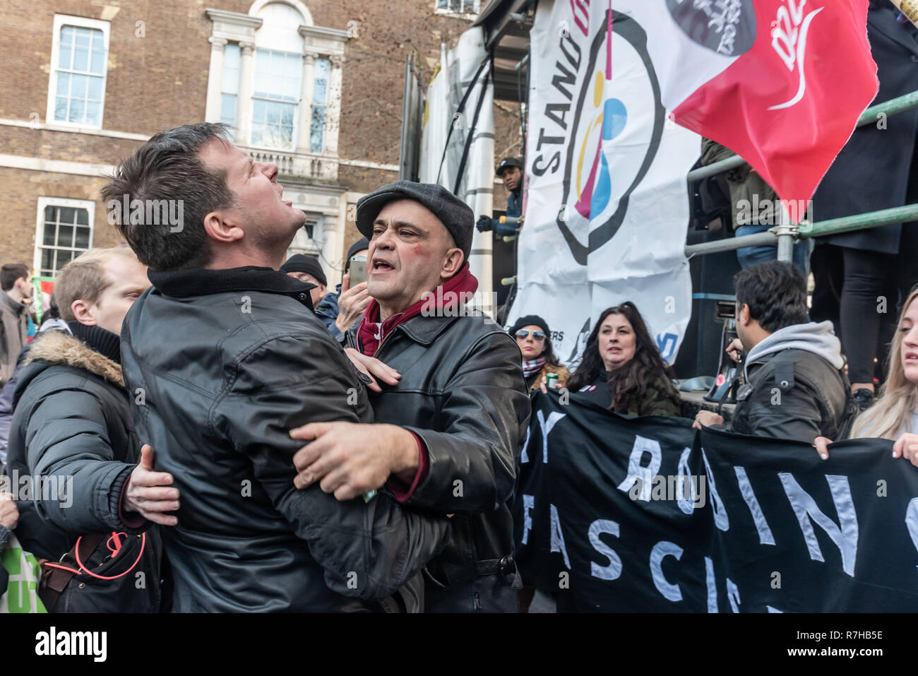 London, UK. 9th Dec, 2018. People argue with a heckler at the rally by united anti-fascists in opposition to Tommy Robinson's fascist pro-Brexit march. The protest by both remain and leave supporting anti-fascists gathered at the BBC and marched to a rally at Downing St. Police had issued conditions on both events designed to keep the two groups well apart. Credit: Peter Marshall/Alamy Live News Stock Photo