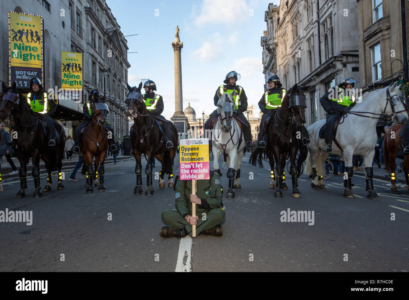 London, UK. 9th Dec, 2018. An anti-fascist demonstrator sits in front of mounted police (Nelson's Column in the background), close to the 'Brexit Means Exit' / 'Brexit Betrayal March' rally. Credit: Graeme Weston/Alamy Live News - Stock Image