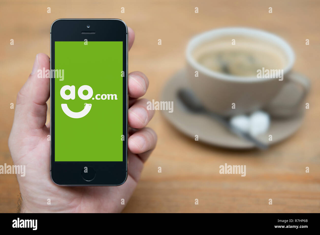 A man looks at his iPhone which displays the AO.com logo (Editorial use only). - Stock Image