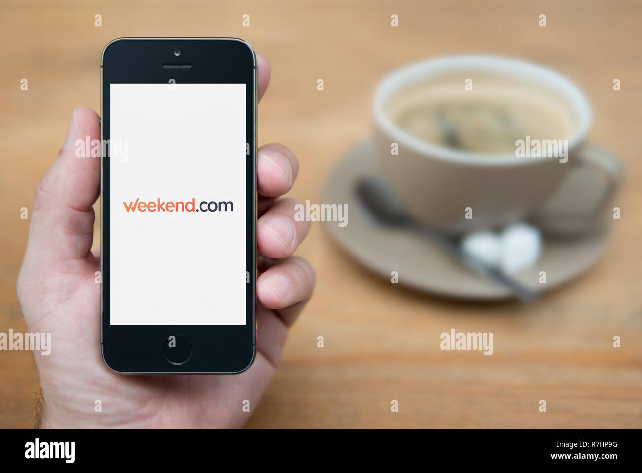 A man looks at his iPhone which displays the Weekend.com logo (Editorial use only). - Stock Image