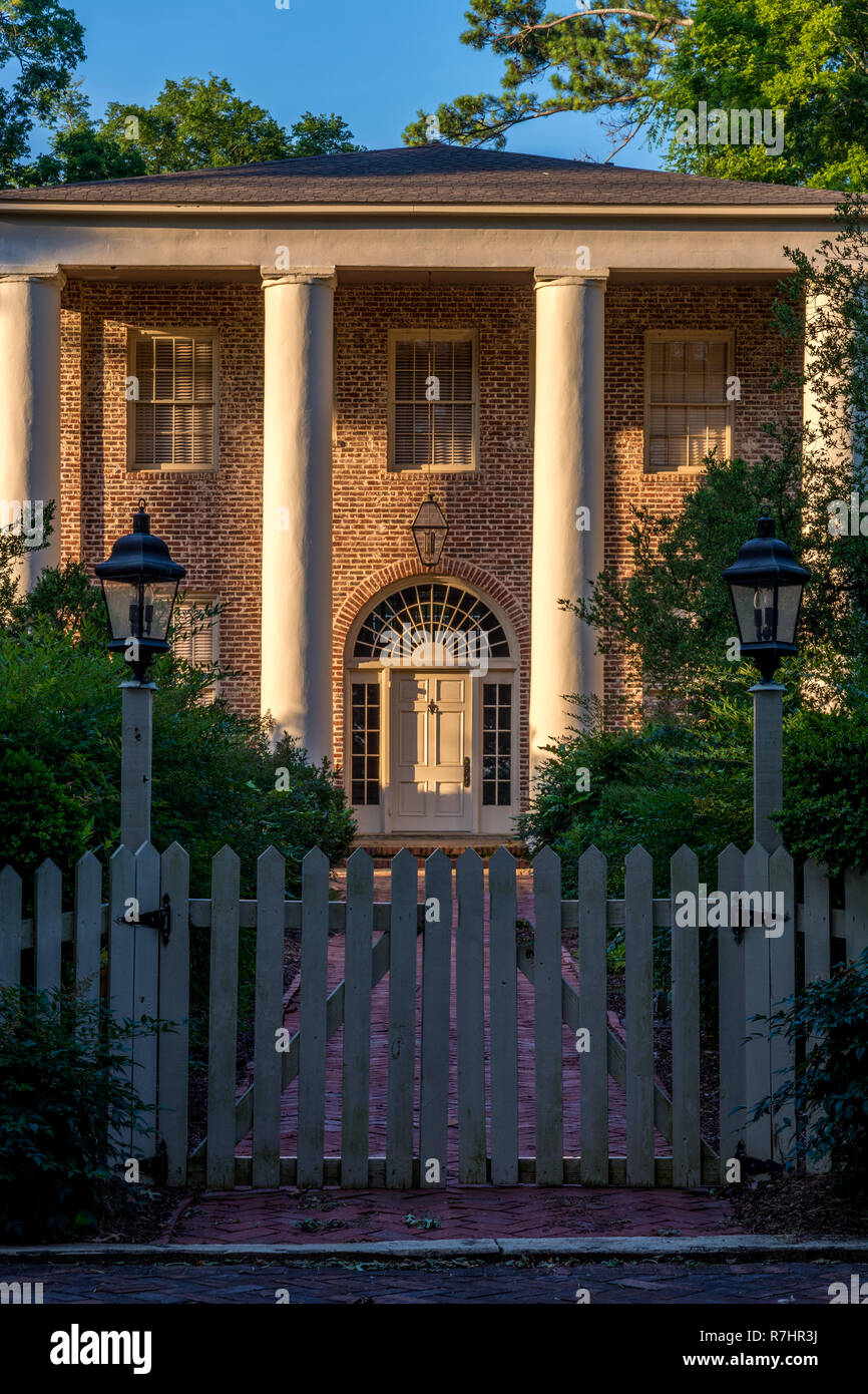 White Picket Fence And Brick House In A Classic Southern Style Stock