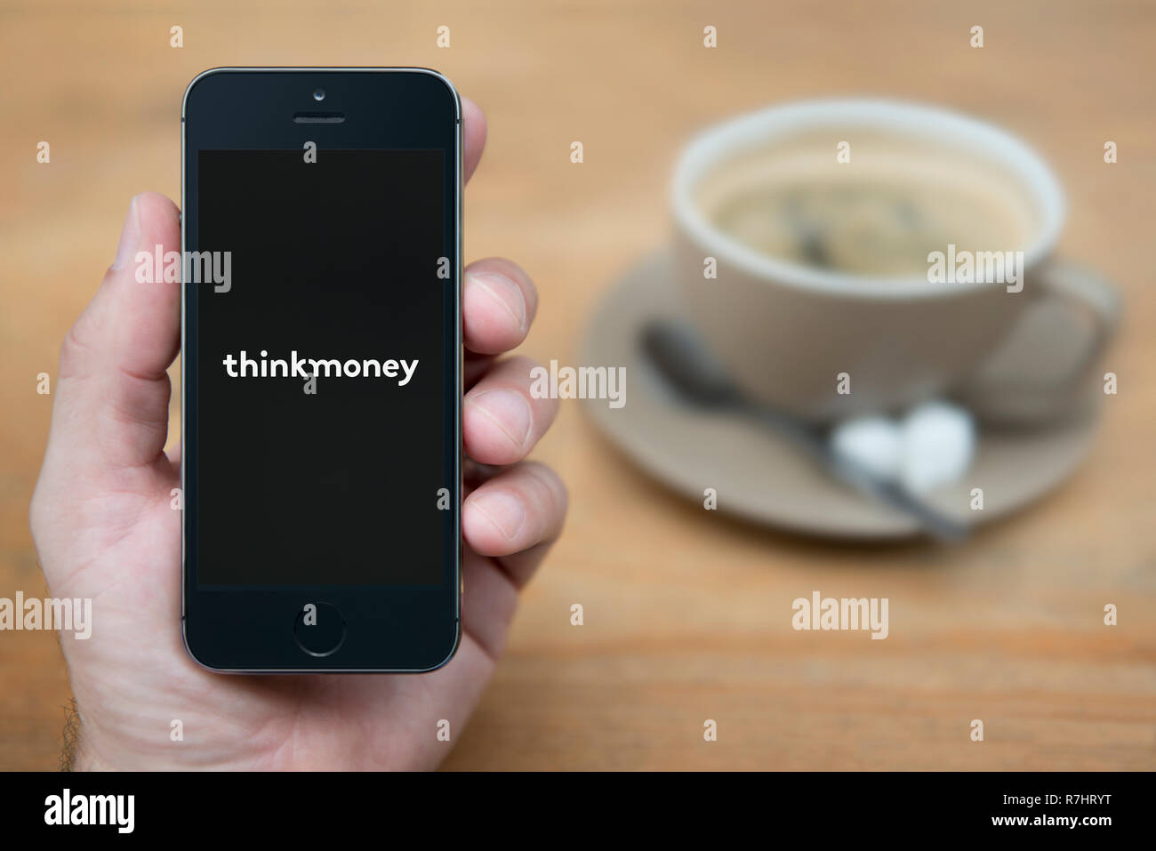 A man looks at his iPhone which displays the ThinkMoney logo (Editorial use only). Stock Photo
