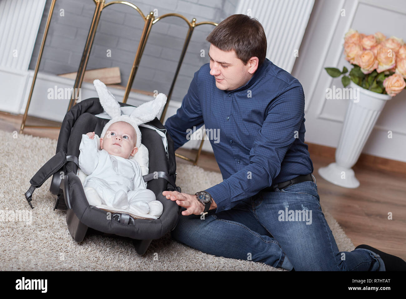 loving dad and a pretty baby in a rabbit costume before a walk - Stock Image