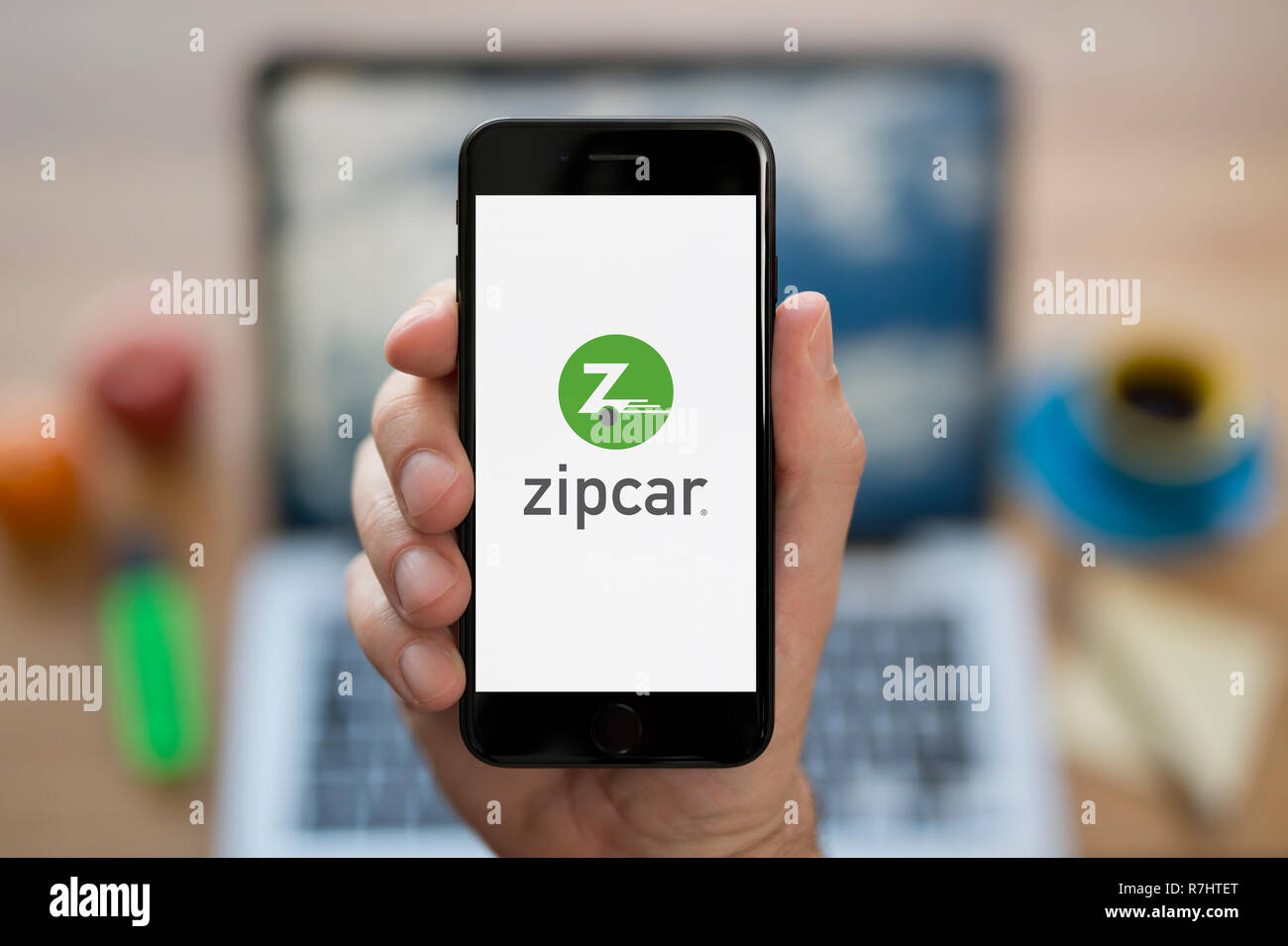 A man looks at his iPhone which displays the ZipCar logo (Editorial use only). - Stock Image