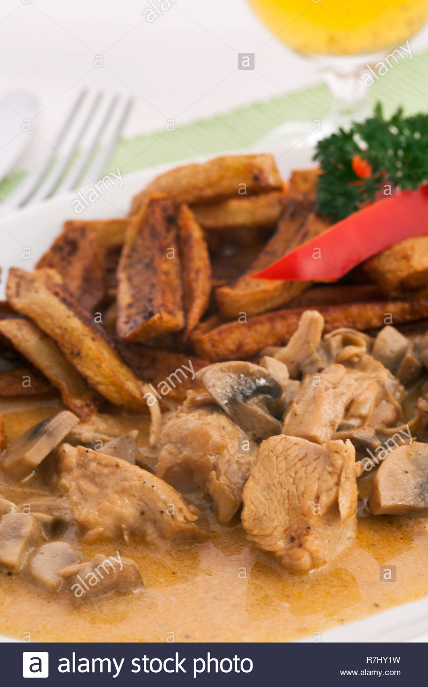 Turkey meat steamed with mushrooms and french fries on a plate and a light green cloth placemats. Decorated with red pepper and parsley. Stock Photo