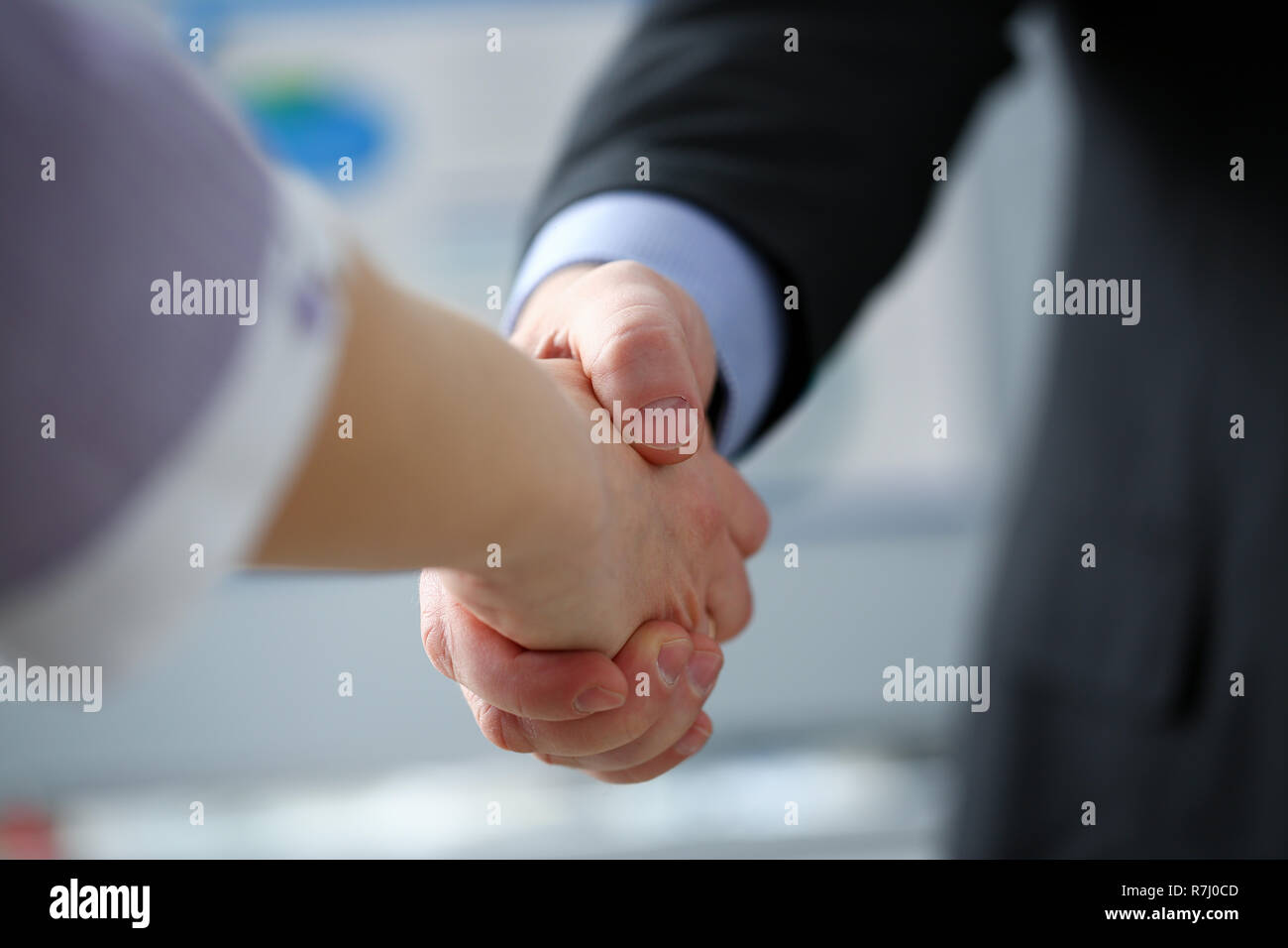 Man in suit and tie give hand as hello in office - Stock Image