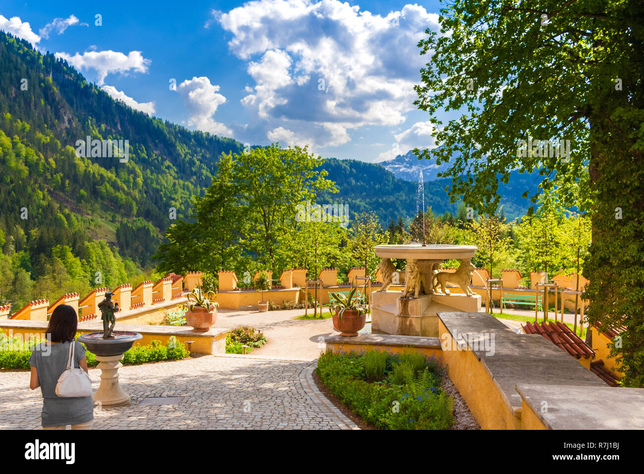 A Woman Admires The Beautiful Garden Of Hohenschwangau Castle With ...