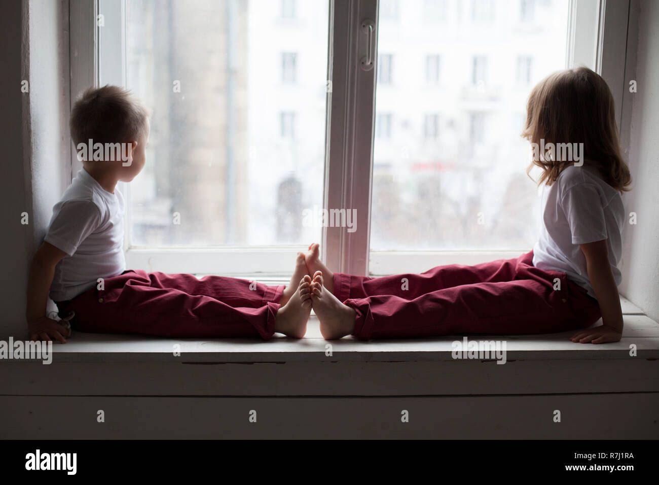little boy and girl sit on the windowsill looking out the window - Stock Image