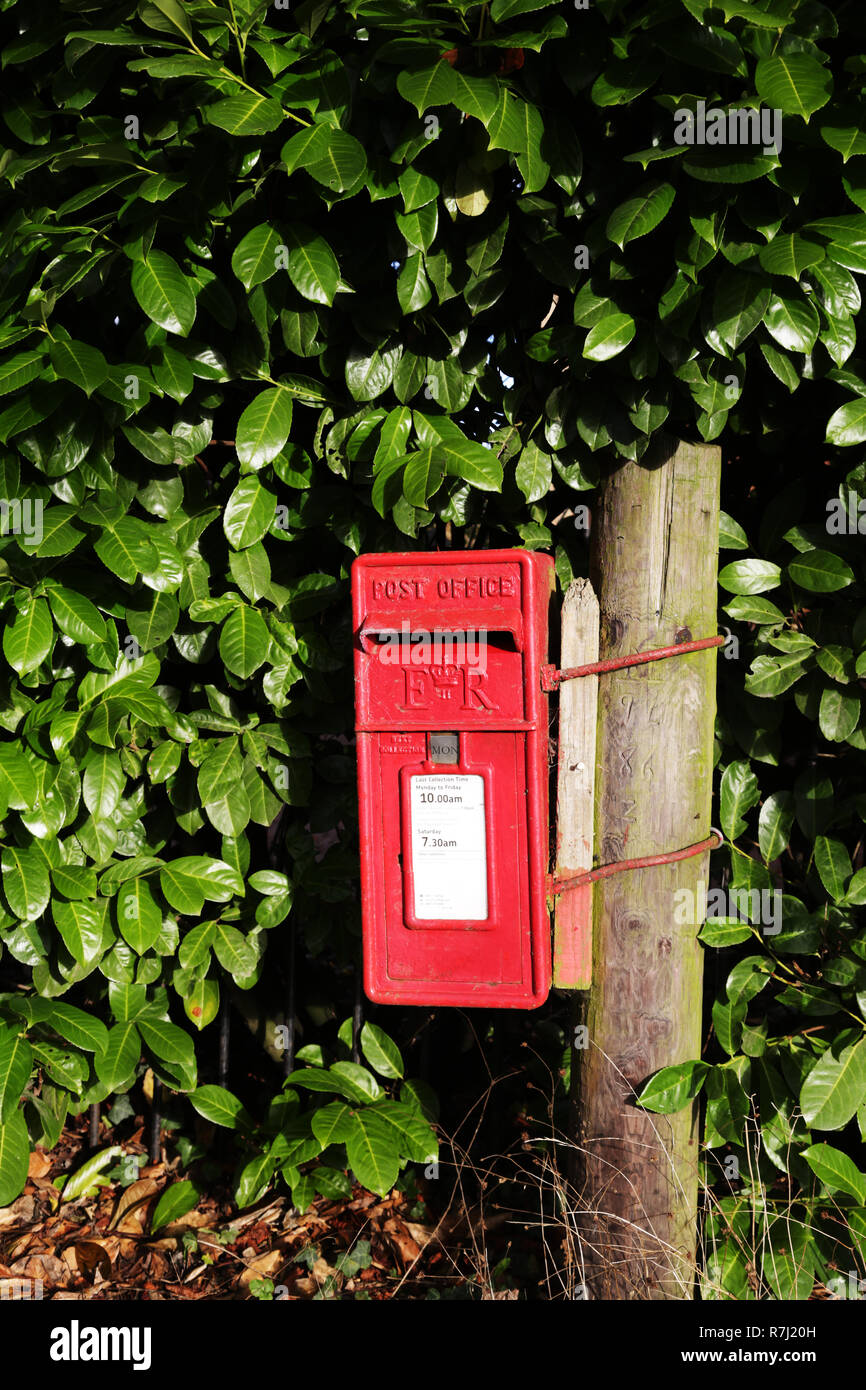 An old red post box in the English countryside. - Stock Image