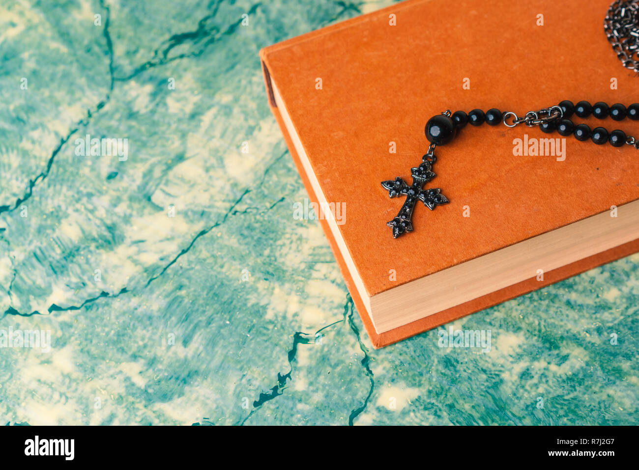 Black rosary and cross resting on the closed book at green table, seen from above.religion school concept.Vintage style. Stock Photo