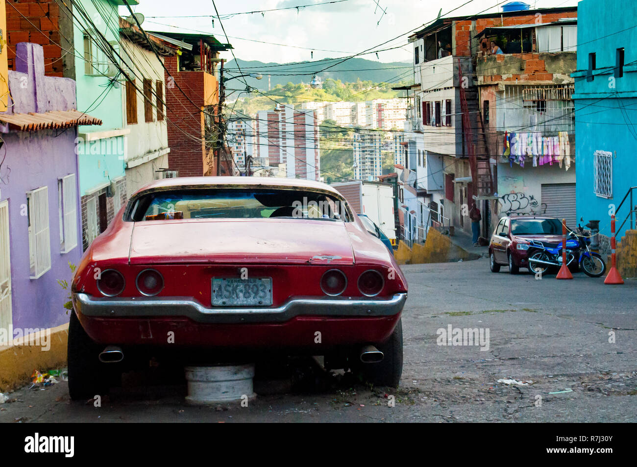 Caracas, Venezuela - 20 june 2018: old american car parked in poor city slum. The country is hit by a severe economic crisis and it's not possible to  - Stock Image