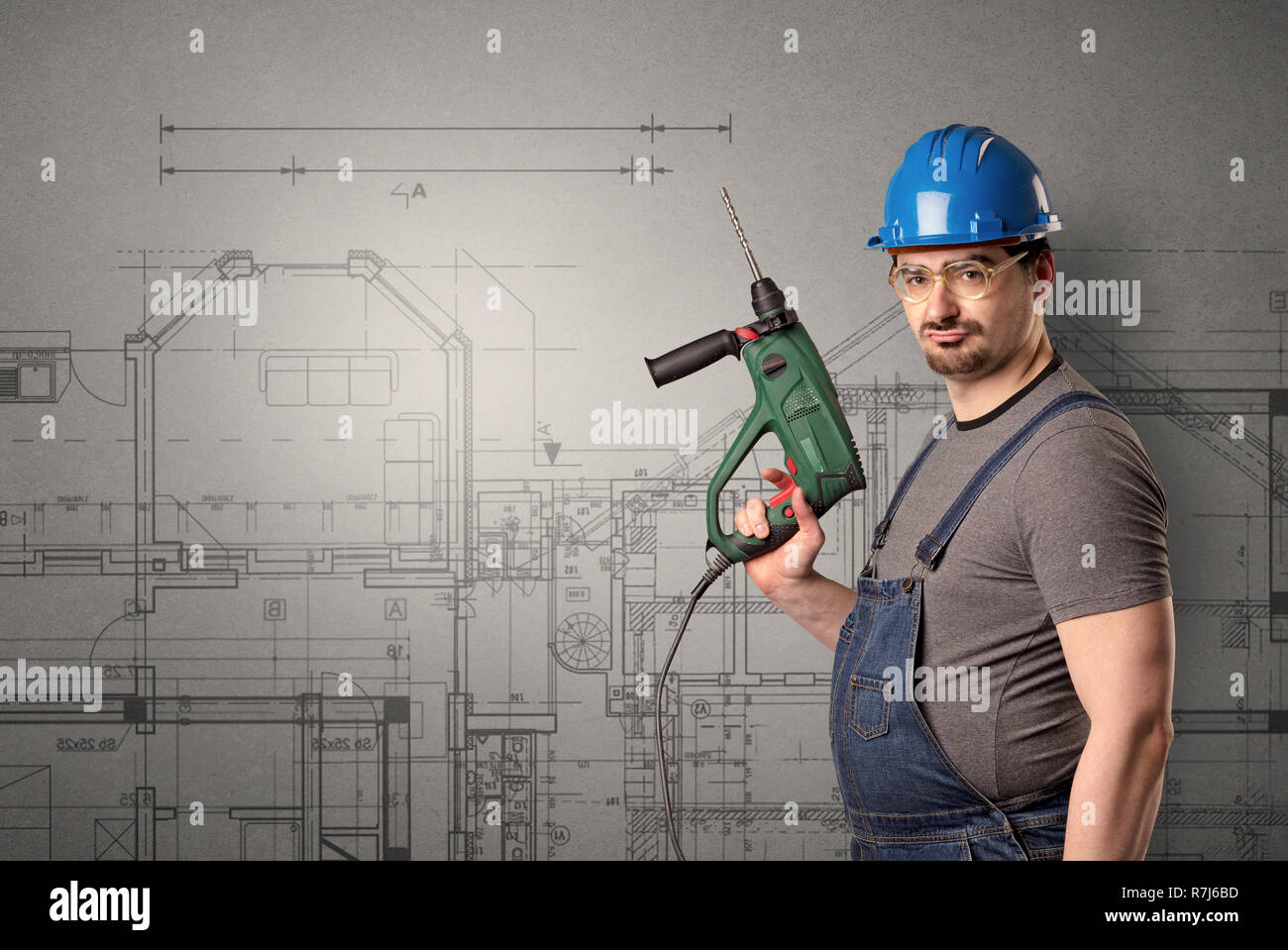 Worker standing with tool in his hand in front of technical drawings. - Stock Image