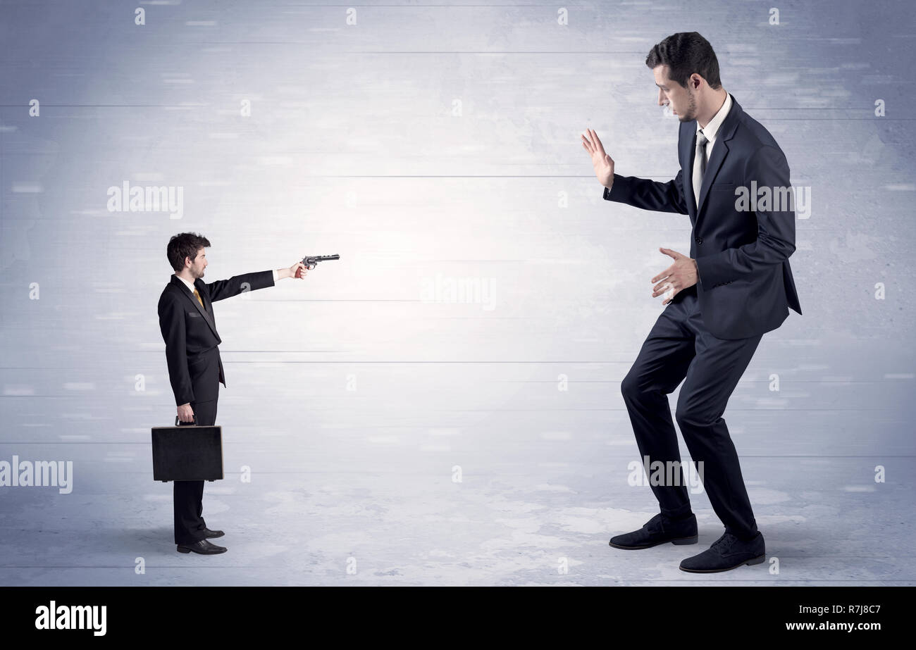 Tiny businessman with gun shooting giant fearful businessman  - Stock Image