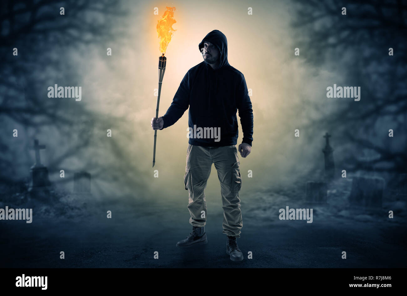 Man with burning flambeau coming from thicket and looking something  Stock Photo