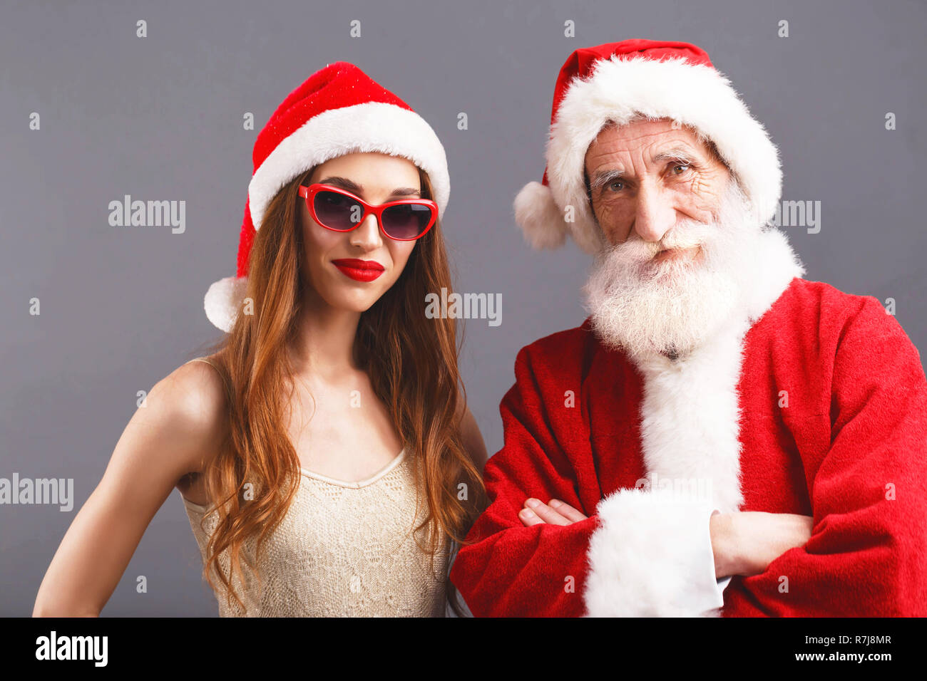 ed658bf1684e7 Santa Claus and young mrs. Claus wearing Santa hat and sunglasses standing  on the gray
