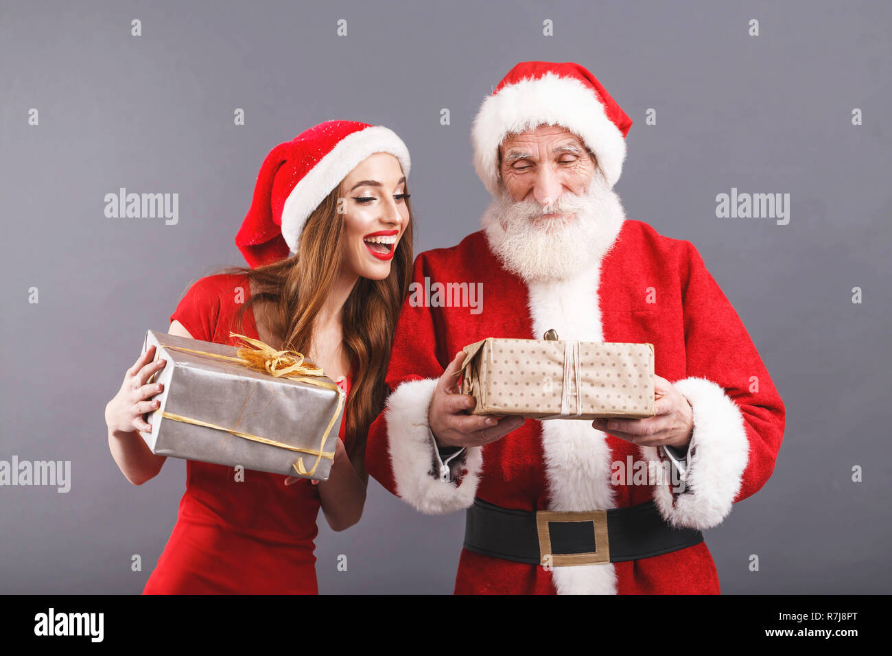 2ebd71efd9c51 Santa Claus with white beard wearing sungasses and young mrs. Claus ...