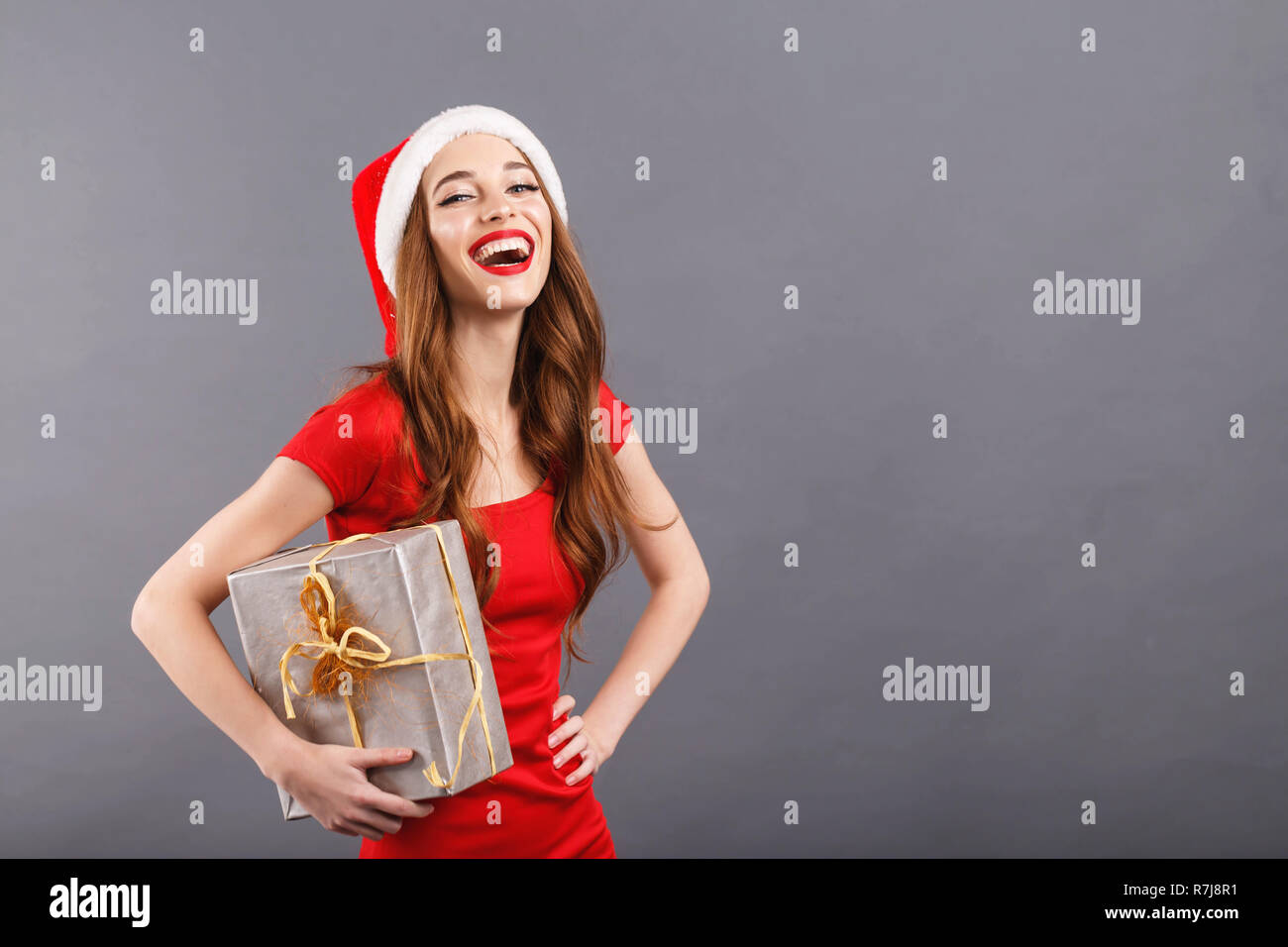 79e125f85c1cc Beautiful christmas woman wearing Santa hat and red dress laughing and  holding a present
