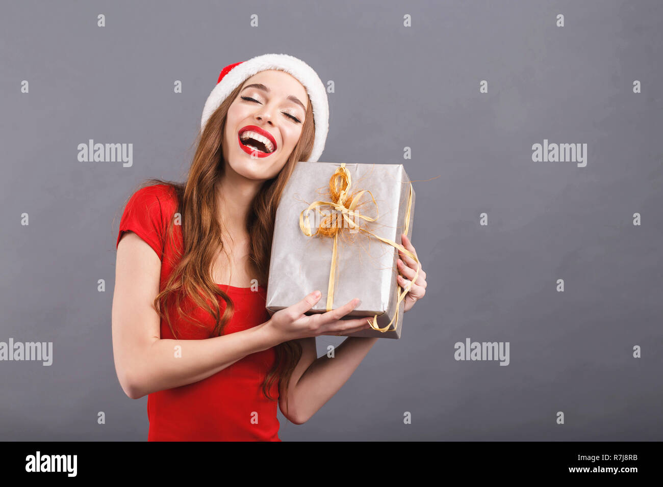 d5ce66d9ccea3 Excited christmas woman wearing Santa hat and red dress laughing and  enjoying of a gift