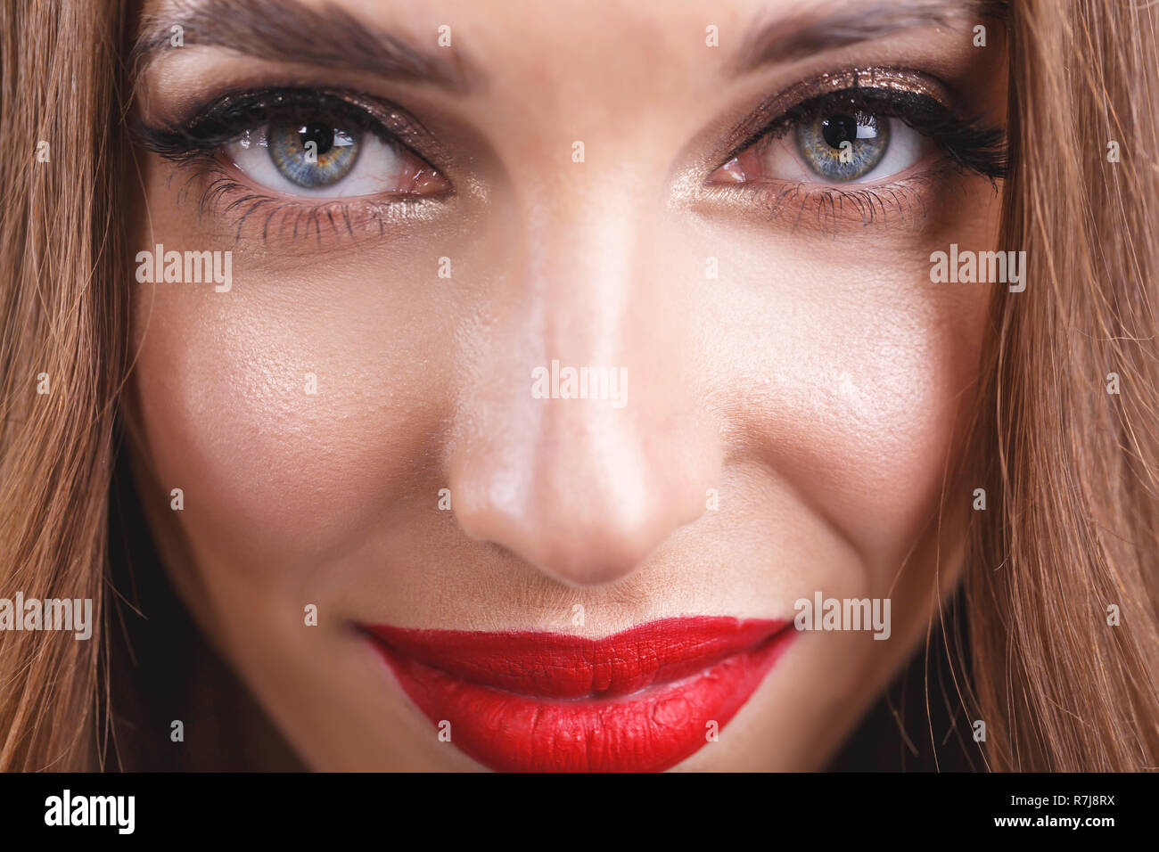 Cropped view of attractive romantic long haired woman with red lips wearing black dress standing on the gray background Stock Photo