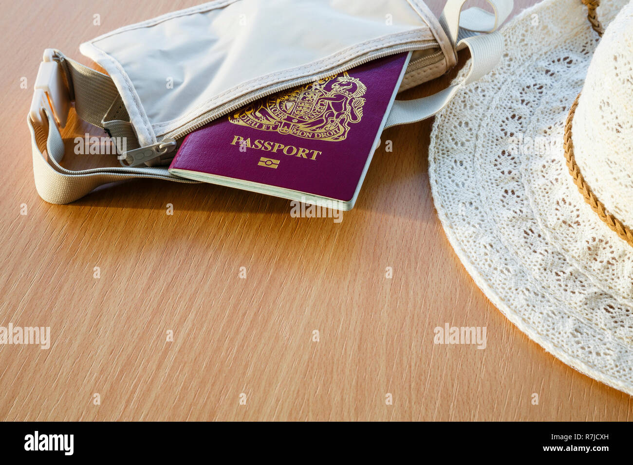Travel things for travelling abroad British biometric passport in a wallet with women's sunhat on a table top. England, UK, Britain - Stock Image