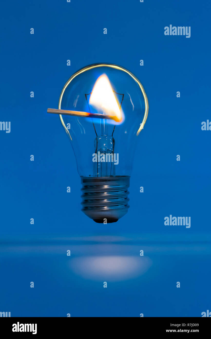 lighted match on a background of the bulb in the dark - Stock Image