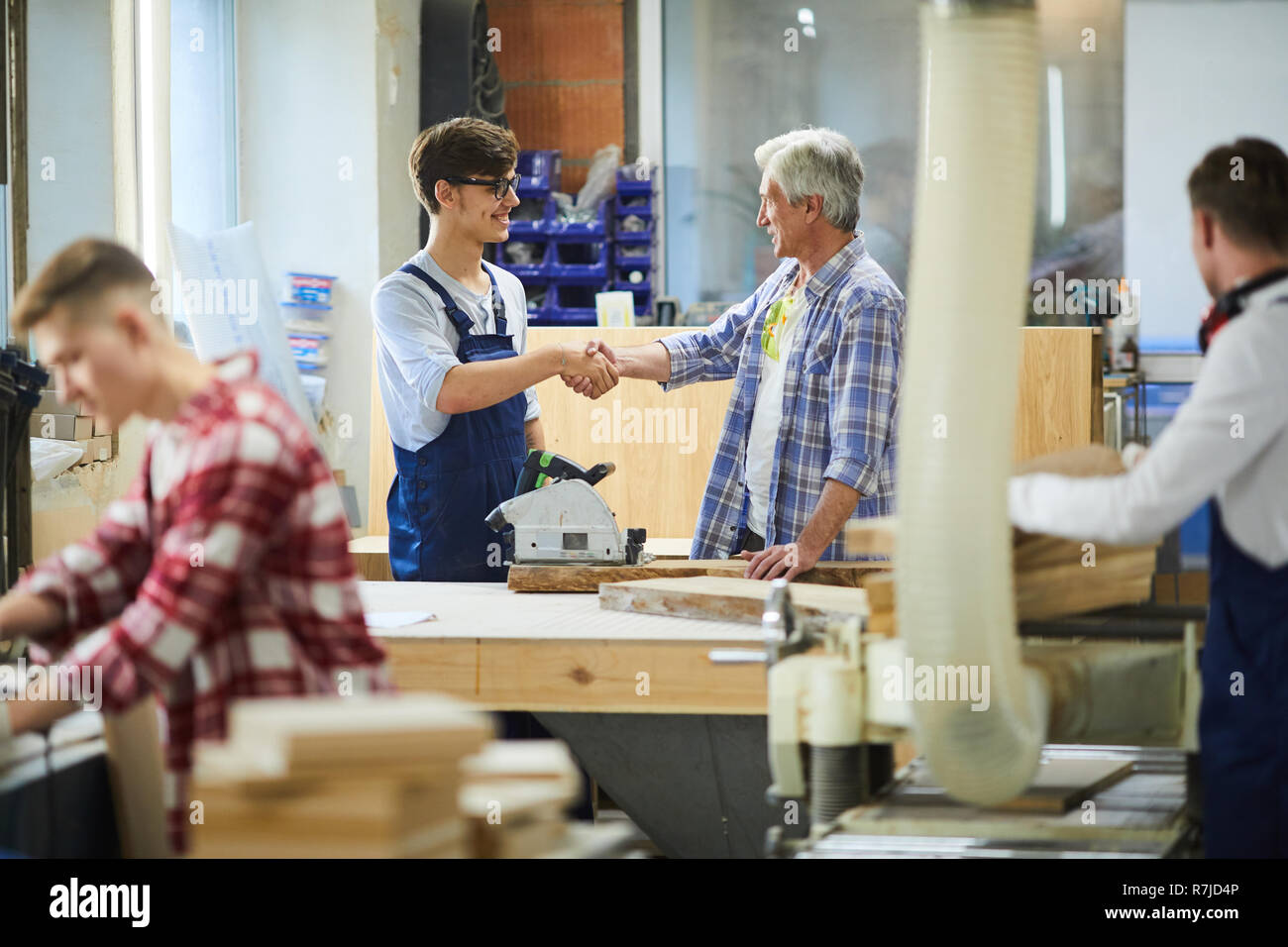 Senior joiner greeting young colleague in factory workshop Stock Photo