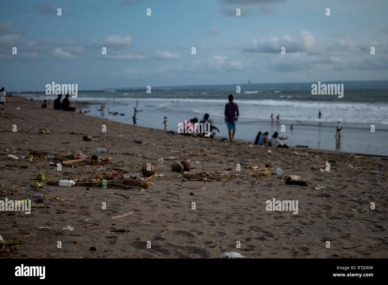 People seat near trash on the Beach, a lot of plastic garbide on the beach of Indian ocean - Stock Image