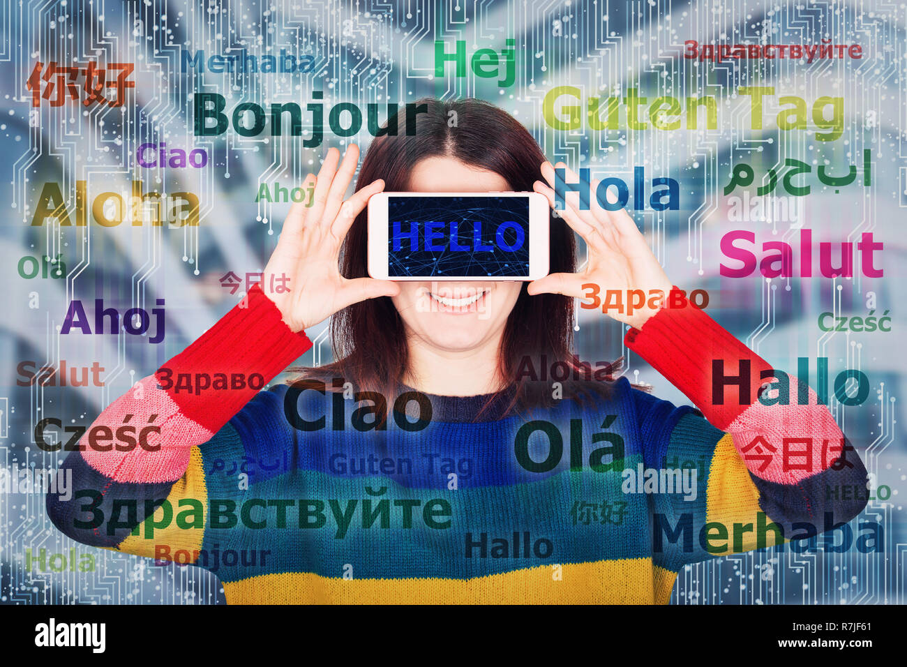 Happy young woman student holding smartphone close to eyes having fun learning and different languages. Speaking many languages easier using modern te - Stock Image