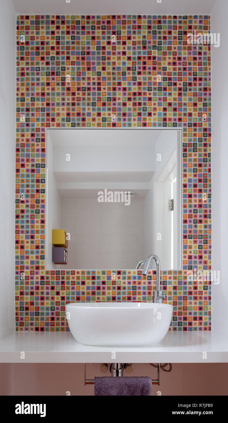 Contemporary bathroom with wash basin, colorful glass mosaic tiles, white painted MDF shelf and mirror inset into the tiles. - Stock Image
