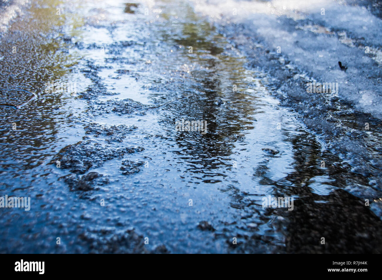 Melting ice on a road - Stock Image
