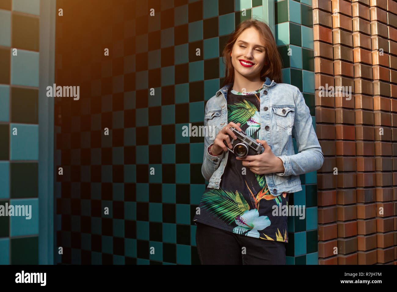 Cool funny girl model with retro film camera wearing a denim jacket, dark hair outdoors over city wall in a cage background. Sun flare Stock Photo