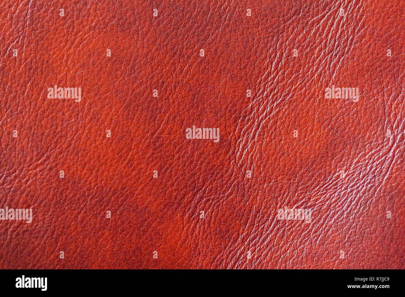 Texture of of genuine leather close-up, with wrinkle, crease, orange brown color, background surface - Stock Image