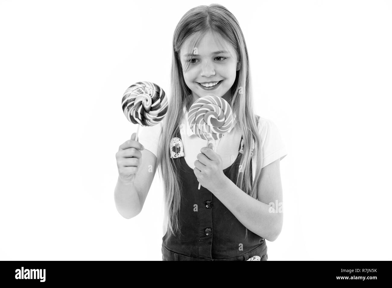 Hard choice. Cheerful little girl holding lollipops in her hands and smiling while standing isolated on white. Girl can not decide which lollipop she wants. Sweets addicted kid wants all candies. - Stock Image